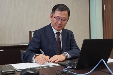 署名するコスモエネルギーホールディングス代表取締役社長 桐山 浩氏