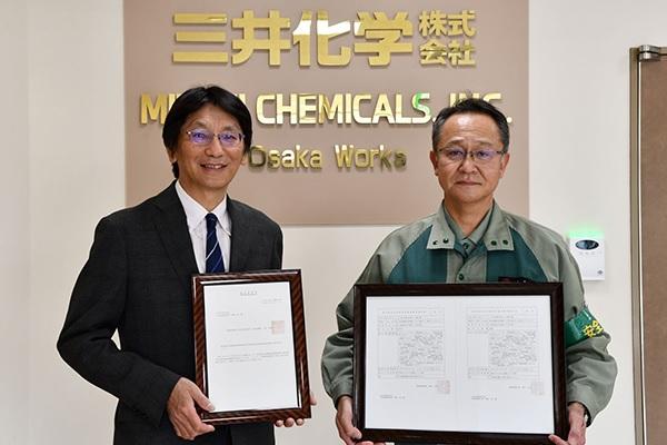 認定証を手にする髙木前工場長(左)と永山安全・環境部長